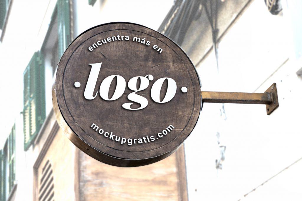 Mockup gratis de un rótulo redondo de madera sobresaliendo de una fachada