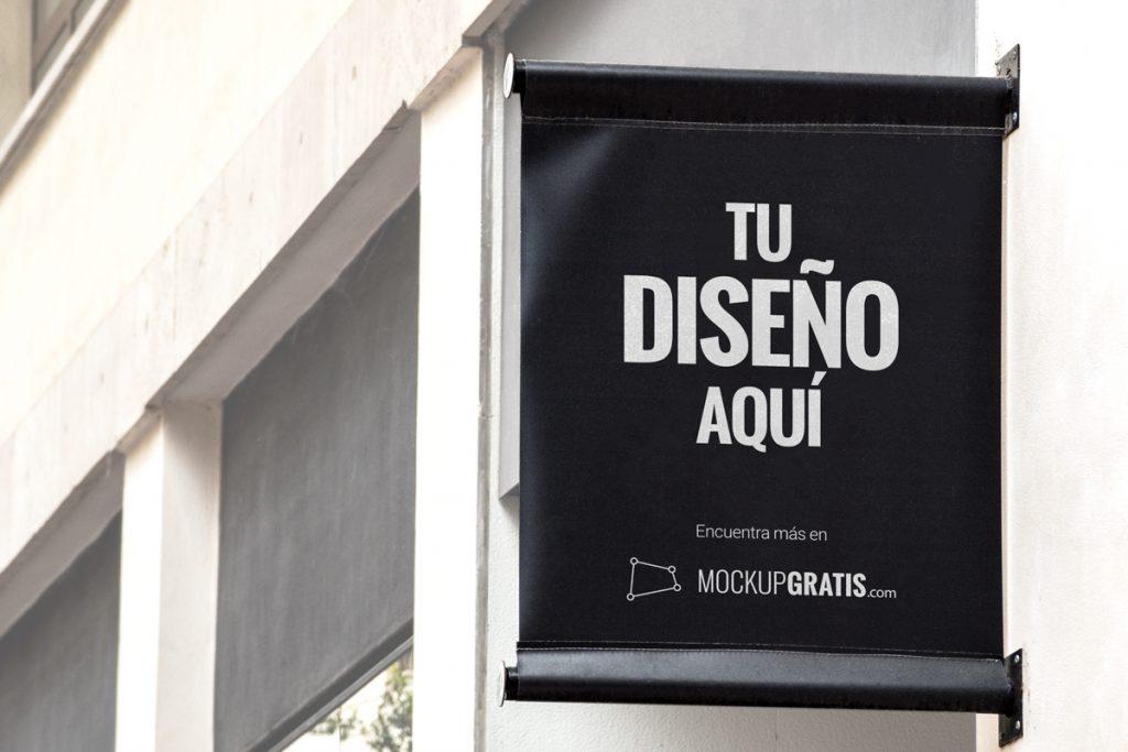 Mockup gratis de una banderola de tela en una fachada, en PSD editable