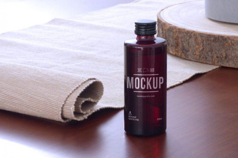 Mockup de un bote de producto de cosmética pequeño sobre un fondo de madera, en formato PSD